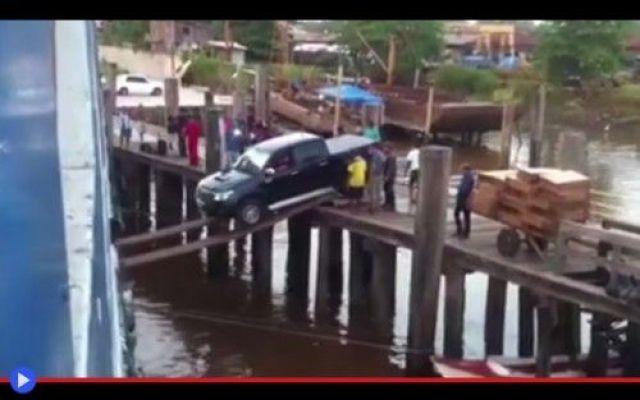 Auto tenta d'imbarcarsi usando due assi di legno Così si è giunti fino a questo attimo di pericolo e profonda paura: un molo stretto, un grosso pick-up Toyota, portuali e stivatori che battono nervosamente il piede. Un'intera carriola di blocchi di #strano #pericolo #trasporti #brasile