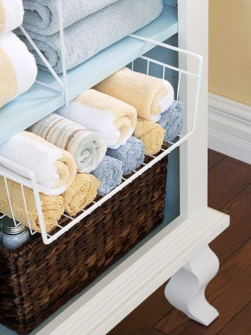 installing off-the-rack storage helpers. A glide-out wire bin holds rolled-up washcloths. On the shelf above, wire shelves separate piles of bulky towels.
