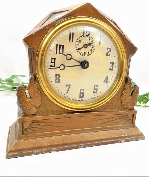 Lux Clock with Rooster Design, Metal Wind Up Clock, Novelty Alarm Clock by Lux Clock Manufacturing Co., Circa 1936. Measures 6 3/8 tall and 6 3/8 wide, with a 3 1/2 paper dial. A lovely brown finished novelty clock with a proud rooster on each side of the face. A perfect alarm clock for guest rooms, your room or in the kitchen. This clock was one of many novelty alarm clocks Lux made, this one circa 1936. With a copper brown finish and the Lux 30 hour wind movement. Uses a wi...