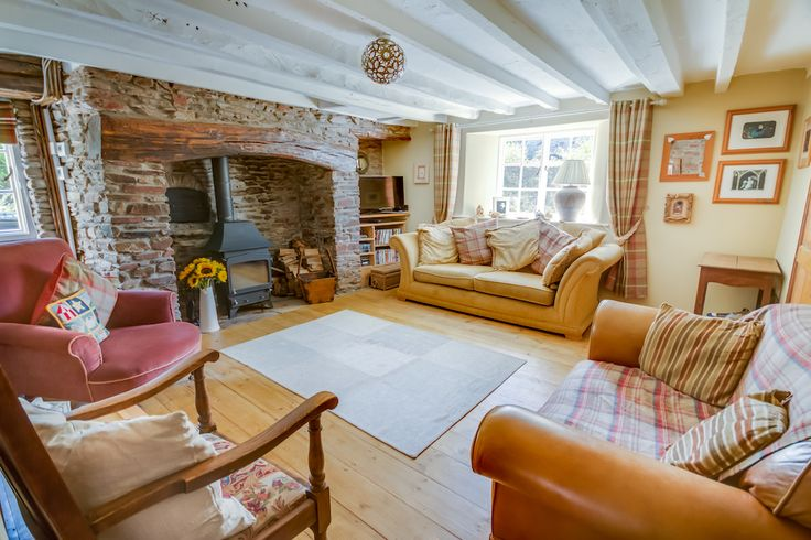 The lounge with large inglenook fireplace and wood burner at Barnfield Holiday Cottage near Exmoor in North Devon.