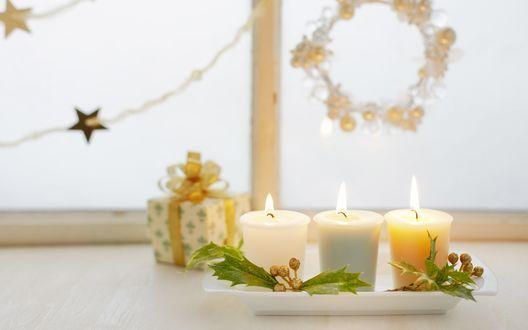 Новогодние свечи, украшенные веточками омелы и маленький подарок у окна