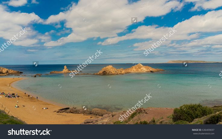 A high view of Cala Pregonda. It is a medium sized golden beach with clear inviting sea protected by curve of the bay. Menorca, Balearic Islands, spain.