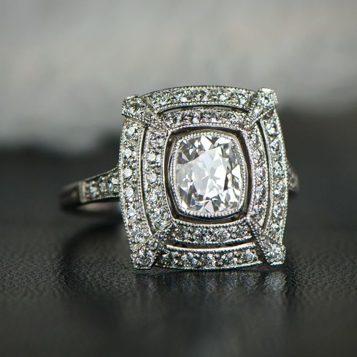 A fantastic double halo cushion cut diamond engagement ring, set in platinum and adorned with diamonds on the shoulders.