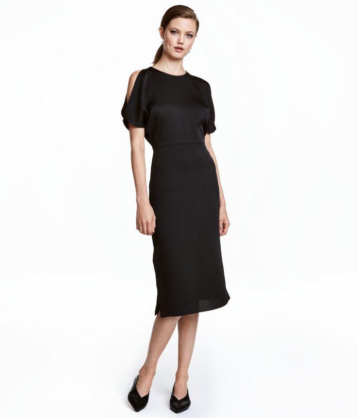 Musta. Polvipituinen mekko kreppikangasta. Koristeaukot olkapäissä. Väljä yläosa ja napitettava niskahalkio. Vyötäröleikkaus ja kapea hameosa, jossa