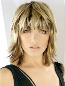 Blonde medium length choppy shag haircut with wispy bangs and dark brown low lights hairstyle