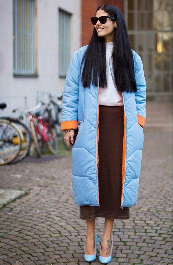 Gilda Ambrosio in a long light blue and orange coat over a brown midi skirt