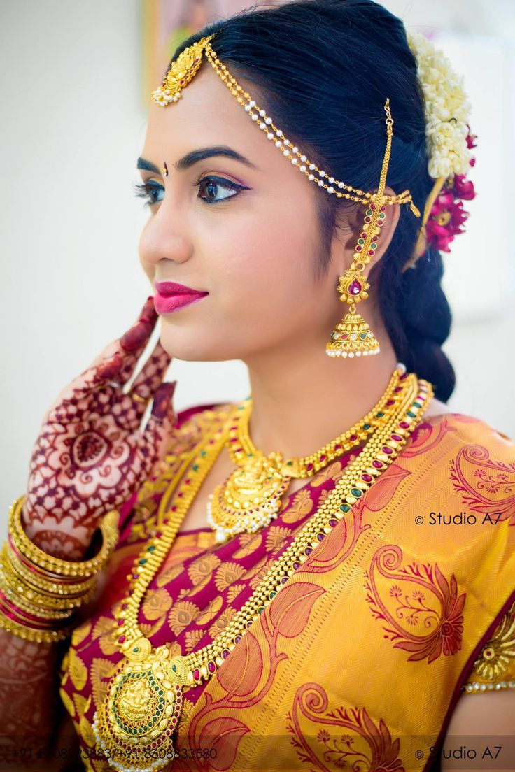 The gorgeous bride with bright orange colour tissue saree brings out her gracefulness and elegance. The short sleeve blouse with zardosi and arey work gives the right mix of tradition, colour and creativity.  Yhe Jewelry part of the bride have Kasumalai, step chain, necklace, big jimkas, heavy Nagas hip belt and heavy matching bangles carry the bride with élan.