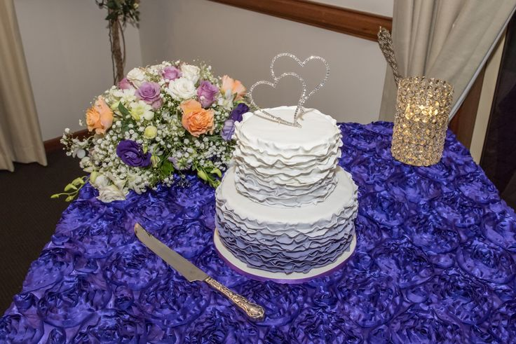 Wedding Photographer - Candid Photos of a Lifetime  White & Purple ruffled wedding cake with diamante hearts topper