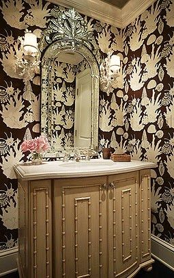 Inside A Palm Beach Bermuda-Style Bungalow - The Glam Pad~A faux bamboo sink, along with Venetian mirror and coral sconces add Palm Beach flair to the powder room.