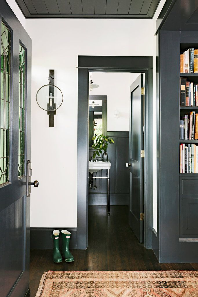 Dark trim matches bookcases, white walls, wood ceiling matches trim, interior door could be an exterior door that shows off cool room through window.