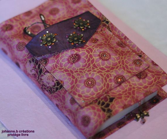 Protège livre en coton fleuri avec poche pour lunettes, mouchoirs, passe navigo et marque page intégré.