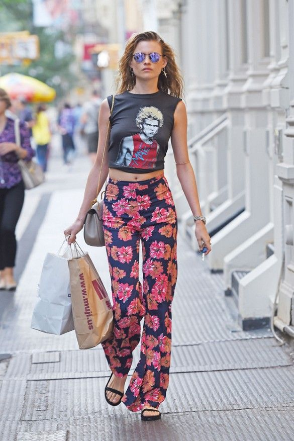 Behati Prinsloo wears a rock n roll cropped tank, floral Reformation pants, sandals, and mirrored sunglasses