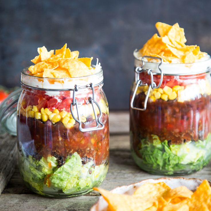 Salat, Hackfleisch, Tomaten, Mais, Bohnen, Crème fraîche und Tortilla Chips im Glas anrichten und Portion für Portion servieren. Partyklassiker 2.0.