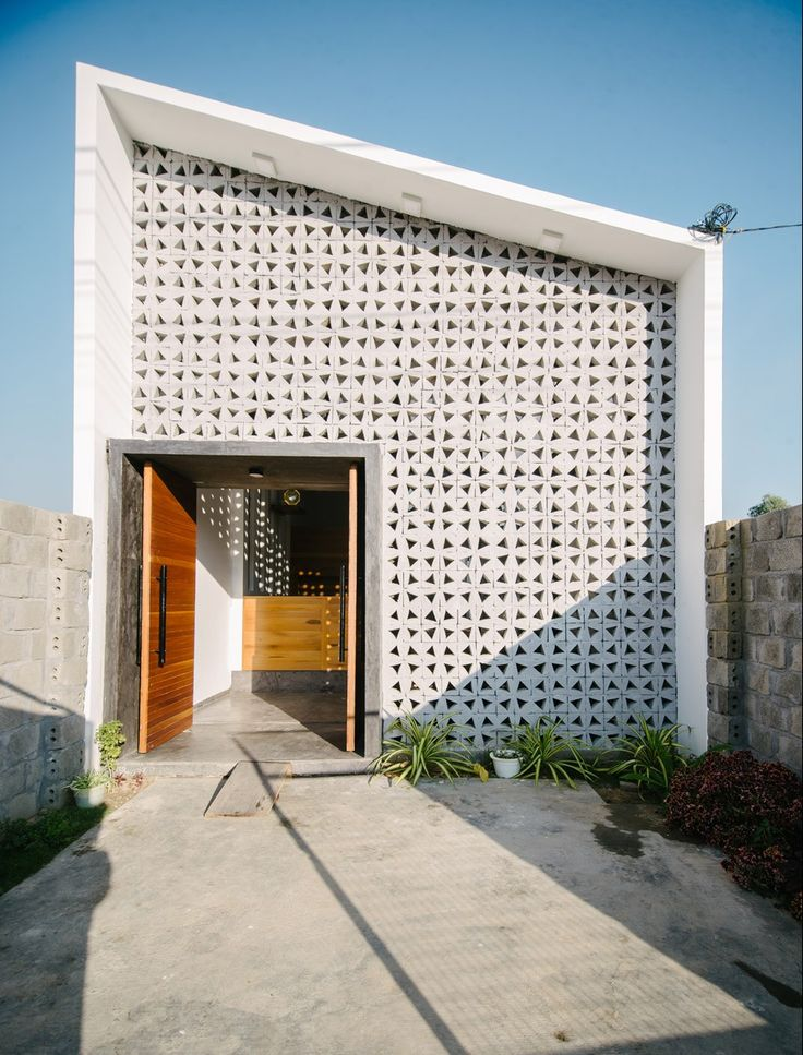 Concrete blocks with triangular apertures allow light to filter into the rooms…