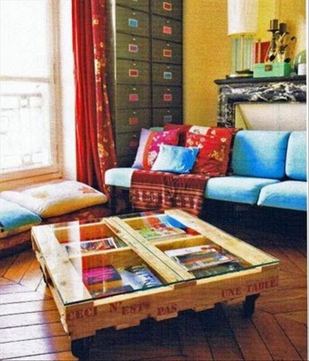 A coffee table with a glass top made from a pallet