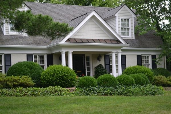 bone painted house with black shutters and planting in front of front porch