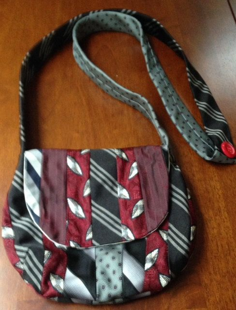 This small, over the shoulder purse is one-of-a-kind and is made from recycled, vintage neckties in colors of black, burgandy and gray. Over the years, I have been given hundreds of neckties from family and friends. Therefore, I have many colors to choose from when making each purse. Usually, I use between six to eight ties of coordinating colors. Measurements for this purse are eight inches wide by seven inches high with a strap that is 48 inches around. This purse features a magnetic…