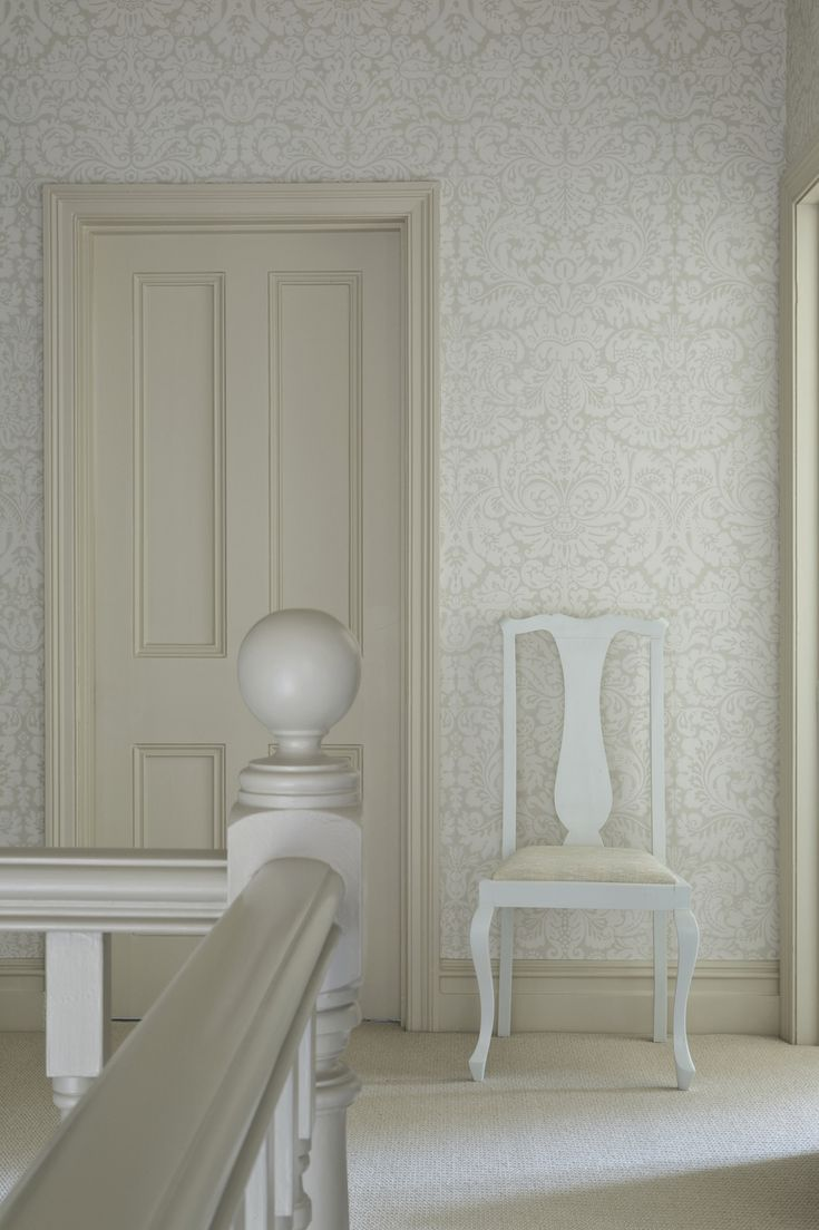 Elegant white wallpaper by Farrow. Loooooove this!!!! And the cream banister.
