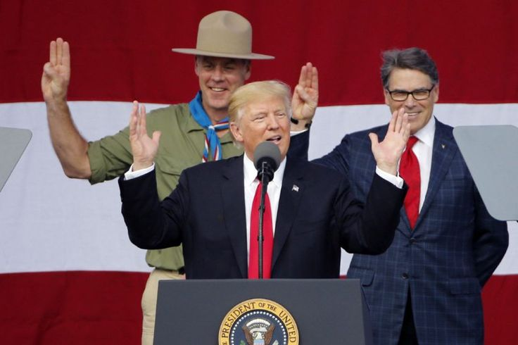 Donald Trump gestures as former boy scouts, Interior Secretary Ryan Zinke, left, Energy Secretary Rick Perry, right, look onat the 2017 National Boy Scout Jamboree at the Summit.
