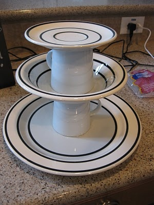 Hot glue on large plate, mug, large bowl, mug, and small plate in a tower to make a fruit stand for a centerpiece.