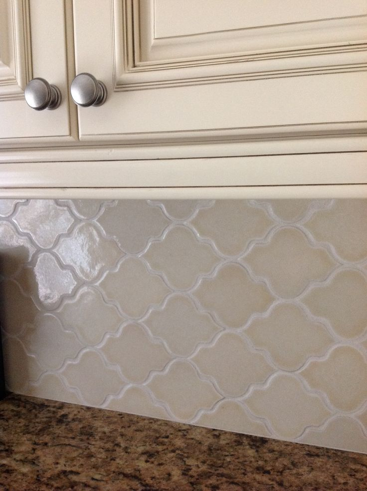 Hand-made. Almond colored glossy arabesque backsplash from Busby-Gilbert. Off white cabinets w mocha glaze & Giallo Ornamental granite