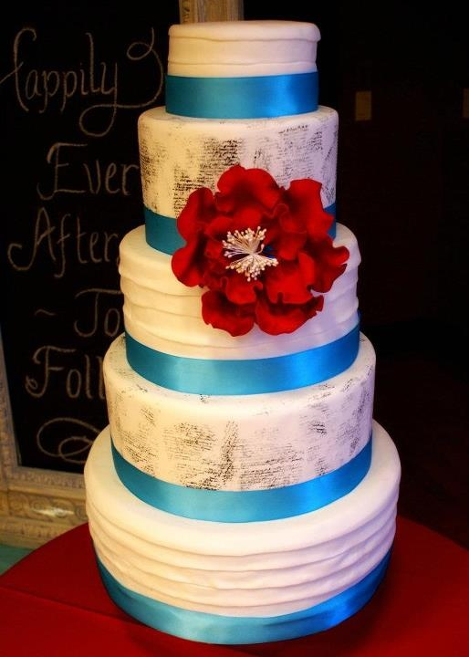 """My wedding cake! White wedding cake with pleats on three layers, and vintage script stamped on two layers. Aqua blue ribbon and big red flower! Chalkboard background """"Happily Ever Afters To Follow"""""""