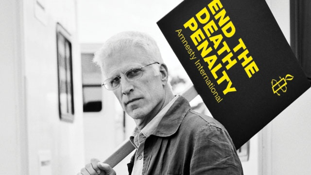 Ted Danson's message to end the death penalty stands out in his grey surroundings.