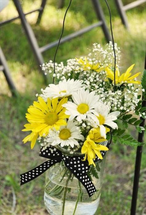 centerpieces-- white and yellow? daisies with black and white polka dotted ribbon