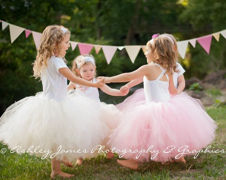 Tea length flower girl tutus in pink, ivory and champagne with satin ribbon ties.