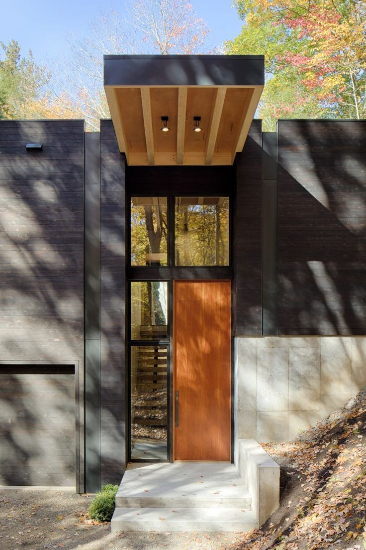 American firm Studio MM Architect has created a modern holiday dwelling for a forested site in upstate New York, which features a giant front door and a garage for its car-lover owner