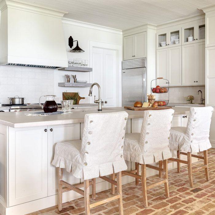 A neutral, coastal open concept kitchen featuring brick floors, sub-zero appliances, custom slip-covered counter stools.
