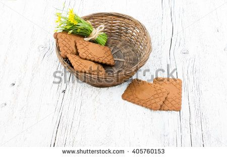 small bouquet of yellow flowers in a wicker basket with cookies on a white wooden background - stock photo