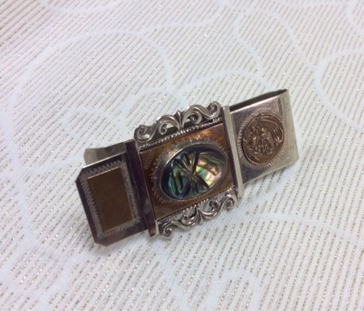 Sterling Money Clip Made in Texco Mexico, Mexican Coat of Arms symble, Abalone Shell or a Stone in Center. With Brass accents. by TrustyThread on Etsy https://www.etsy.com/listing/203170372/sterling-money-clip-made-in-texco-mexico