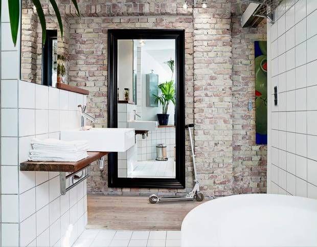 100 års gammel maling og puds er banket af endevæggen i badeværelset, så den i dag fremstår rå og upoleret. Et modigt modspil til det moderne hvide badeværelse. Løbehjulet, der står op ad det store sorte spejl, bruges til at komme rundt i den 176 kvm. rummelige lejlighed.