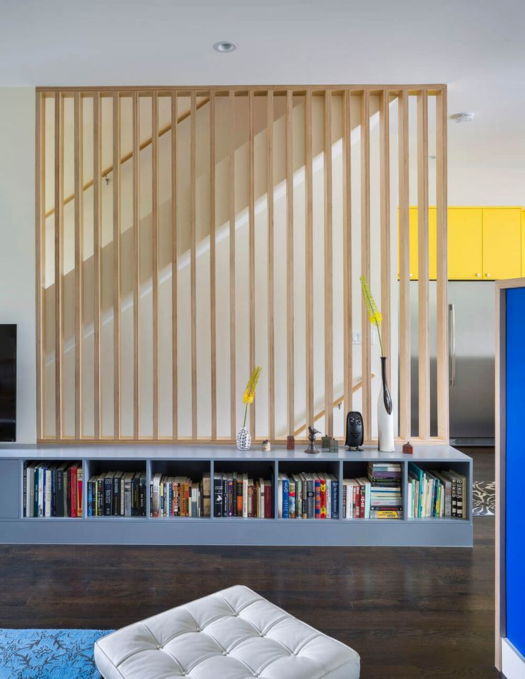 1653 Residence by Studio Build | Staircase with simple linear wood screen and low built-in bookcase
