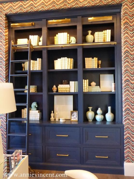 Street of Dreams Arizona - Via Annie Vincent Interiors - Incredible home office with graphic grasscloth wallpaper framing a navy blue built-in bookcase accented with brass cabinet pulls and brass picture lights along with a sliding library ladder on a brass rail.