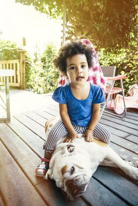 Mixed race girl sitting on dog on porch - stock photo