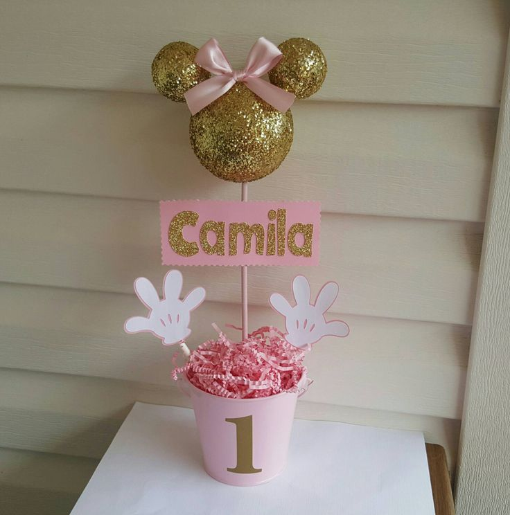 (Please leave a NAME and AGE for centerpiece, if this is not included on payment time, then you will receive centerpiece with out them)  This is a really cute centerpiece to decorate your party.   Minnie mouse foam head: covered with gold glitter, decorated with satin ribbon bow, head is made with a 3.5 foam ball and 2 2 balls used for the ears.  Minnie hands: made of cardstock and each measure about 2.75  Name: made of cardstock and it measure about 2.5 high.  Pail: 4 high TOPIARY SIZE: all…