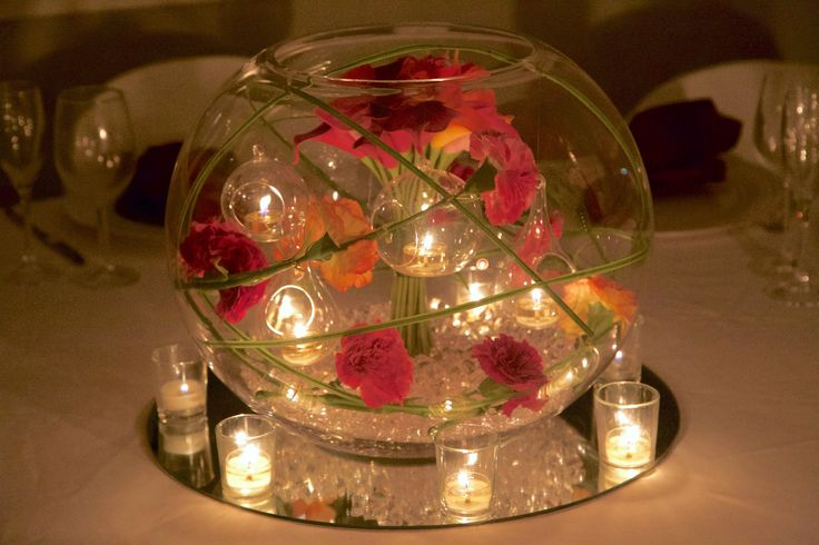 XL fishbowl centrepiece lined with colourful carnations and calla lily's with floating baubles and votives.