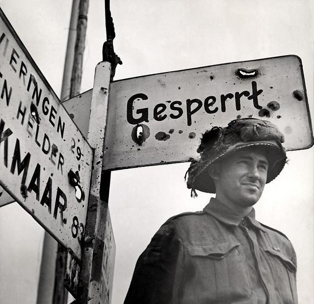 Liberation of Holland. One of the Canadian liberators standing next to a German signpost in Zurich, The Netherlands, April 1945.  Nationaal Archief on Flickr
