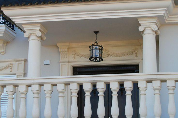 Columnas para porche de entrada con molduras de piedra artificial para puerta.