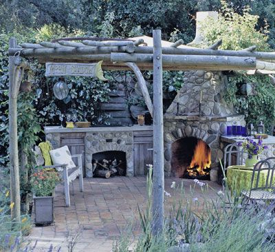 A rustic pergola gives structure to this kitchen area that is centered around a stone fireplace. Simple accents such as benches, containers, and furniture enhance the style of this casual setting.