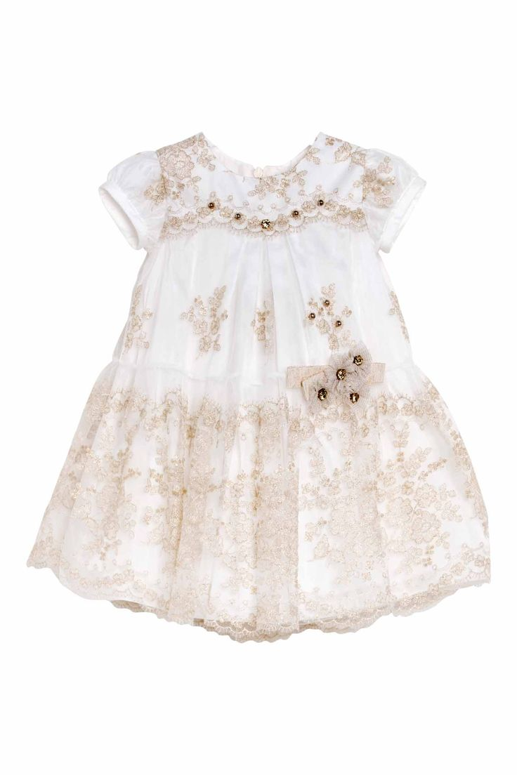 """Newborn dress of our line """"Lesy Ceremony"""" in beautiful golg embroidered tulle. The scalloped bodice with short sleeves is embellished by a crystal and gold pearls sewn by hand one by one. The skirt has a scalloped ruffle completely embroidered with gold lurex thread and is decorated with a composition of tulle flowers, ribbon bow and shiny gold stones hand sewn."""