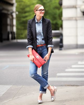 Model in black blazer, jean button up, red belt, jeans, red clutch, silver flats