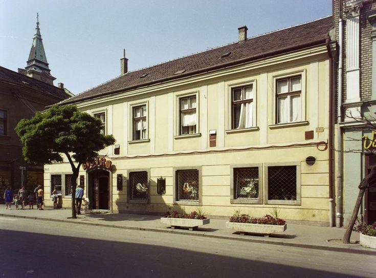 Fő (Március 15.) utca 1., Juhász Gyula utca sarok, háttérben a Szent Imre-templom tornya.