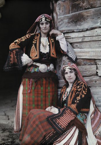 Two young women pose in elaborately sewn, traditional clothing.  Location:Chepelare, Bulgaria  Photographer:WILHELM TOBIEN/National Geographic Stock