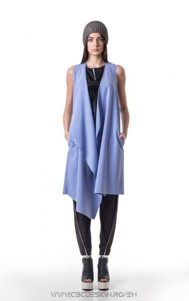 Oversized asymmetrical vest from blue softshell fabric, warm-keeeper and waterproof, with side pockets. It's a versatile item, it's loose fit allows it to be worn in multiple outfits through styling, either over tops or under jackets. it's bright yet cool color transforms the GLACIER Vest into a must-have winter item.