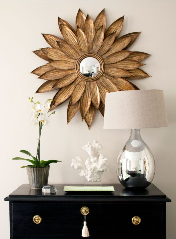 A gold sun burst framed mirror, silver base table lamp and a collection of natural artifacts an assortment of decor items....interesting composition..