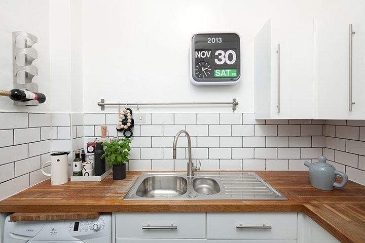 "Credit: Neale Smith In the snug kitchen, dark grey grouting adds definition to white Metro tiles; and Muuto's ""Bulky"""