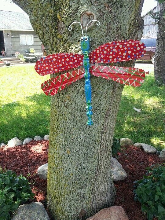 Butterfly or a Dragonfly made from old table leg and paddles from a fan and then painted.